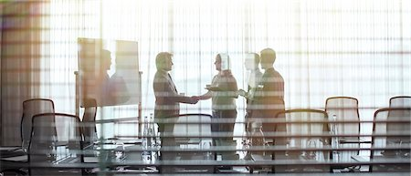 Business people standing in conference room shaking hands Stock Photo - Premium Royalty-Free, Code: 6113-07906001