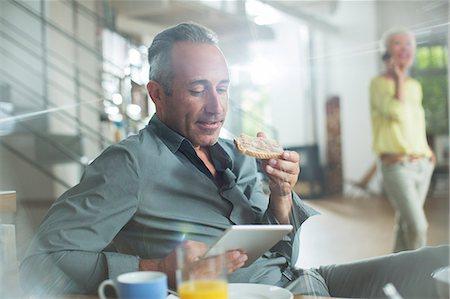 Older man using digital tablet at breakfast table Stock Photo - Premium Royalty-Free, Code: 6113-07906148