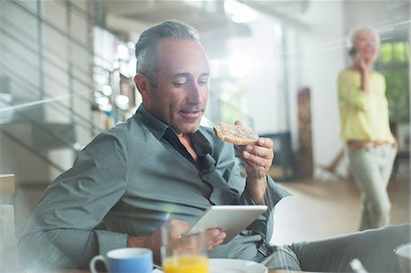 Older man using digital tablet at breakfast table Stock Photo - Premium Royalty-Free, Code: 6113-07906148