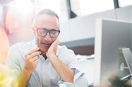 Businessman listening to earbuds at office desk Stock Photo - Premium Royalty-Free, Code: 6113-07906150