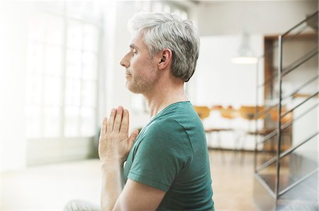 Older man meditating indoors Stock Photo - Premium Royalty-Free, Code: 6113-07906157