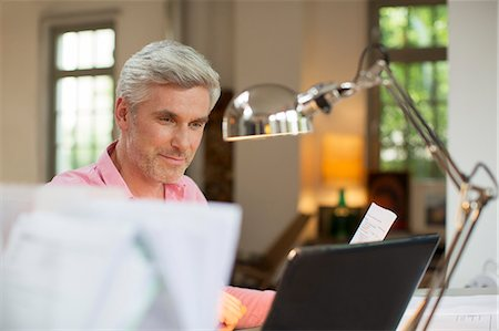 Older man using laptop in home office Stock Photo - Premium Royalty-Free, Code: 6113-07906159