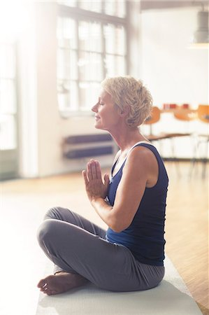 Older woman meditating on exercise mat Stock Photo - Premium Royalty-Free, Code: 6113-07906163