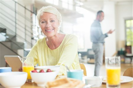 Older woman using digital tablet at breakfast table Stock Photo - Premium Royalty-Free, Code: 6113-07906165