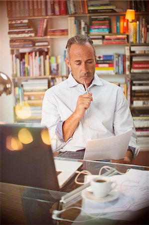 Businessman reading paperwork at home office desk Stock Photo - Premium Royalty-Free, Code: 6113-07906169