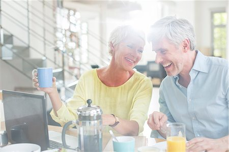 Older couple laughing together at breakfast table with laptop Stock Photo - Premium Royalty-Free, Code: 6113-07906189