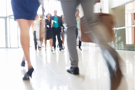 Legs of businesswoman and businessman carrying hand luggage walking through lobby of conference center Stock Photo - Premium Royalty-Free, Code: 6113-07906101