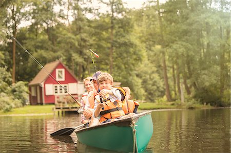 Father and sons fishing from canoe in lake Stock Photo - Premium Royalty-Free, Code: 6113-07906347