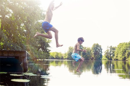 Father and son jumping into lake Stock Photo - Premium Royalty-Free, Code: 6113-07906350