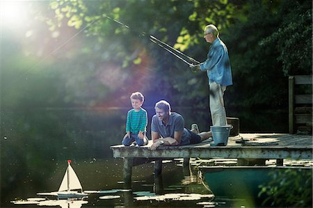 Boy fishing and playing with toy sailboat with father and grandfather at lake Stock Photo - Premium Royalty-Free, Code: 6113-07906352