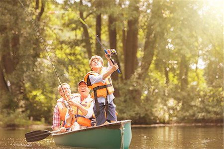 Boy, father and grandfather fishing from canoe on lake Stock Photo - Premium Royalty-Free, Code: 6113-07906369