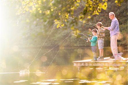 Grandfather and grandsons fishing at lake Stock Photo - Premium Royalty-Free, Code: 6113-07906373