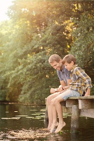 dangling - Father and son dangling feet in lake Stock Photo - Premium Royalty-Free, Code: 6113-07906374