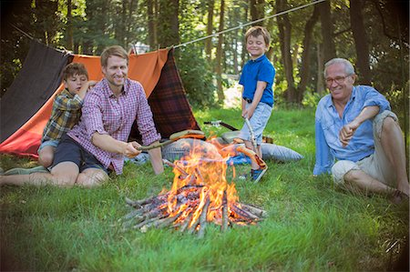 Boy, father and grandfather relaxing near campfire Stock Photo - Premium Royalty-Free, Code: 6113-07906376