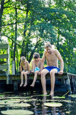 dangling - Father and sons dangling feet in lake Stock Photo - Premium Royalty-Free, Code: 6113-07906383