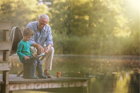 Grandfather and grandson reading at lake Stock Photo - Premium Royalty-Free, Code: 6113-07906393