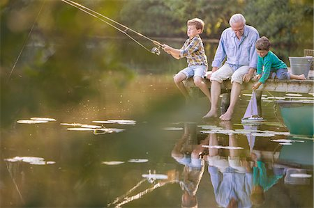 Grandfather and grandsons fishing and playing with toy sailboat at lake Stock Photo - Premium Royalty-Free, Code: 6113-07906390