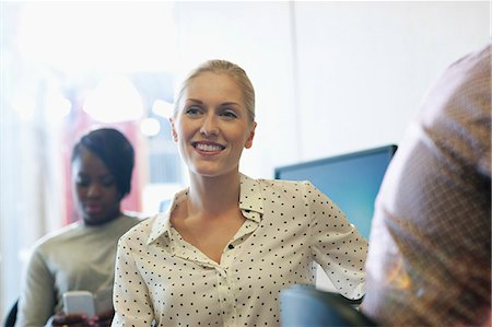 Smiling university student listening to seminar, young woman texting in background Stock Photo - Premium Royalty-Free, Code: 6113-07906461