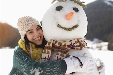 southeast asian ethnicity - Portrait of smiling woman hugging snowman Stock Photo - Premium Royalty-Free, Code: 6113-07906604