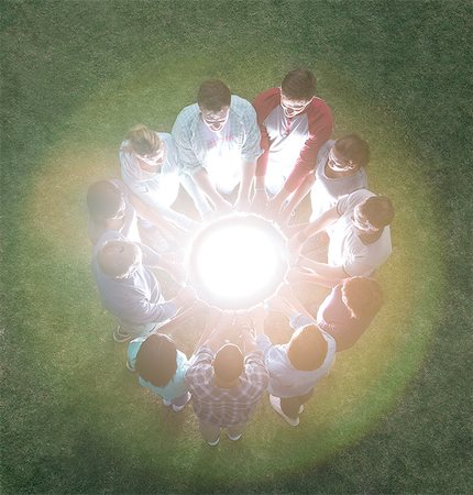 Team in circle surrounding glowing orb Stock Photo - Premium Royalty-Free, Code: 6113-08087944