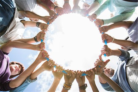 Team forming connected circle surrounding plastic hoop Stock Photo - Premium Royalty-Free, Code: 6113-08087958