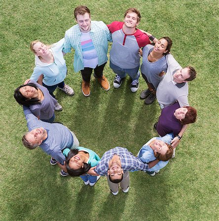Team forming connected circle basking in sunny field Stock Photo - Premium Royalty-Free, Code: 6113-08087917