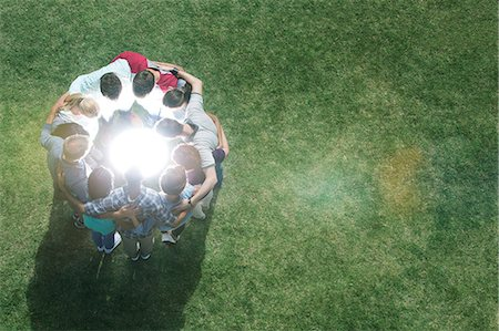 Team huddled in circle around glowing orb in field Stock Photo - Premium Royalty-Free, Code: 6113-08088060