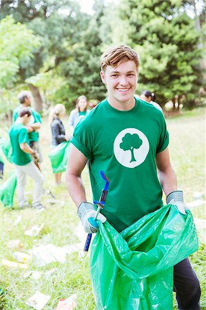 Portrait of smiling environmentalist volunteer picking up trash Foto de stock - Royalty Free Premium, Número: 6113-08088062