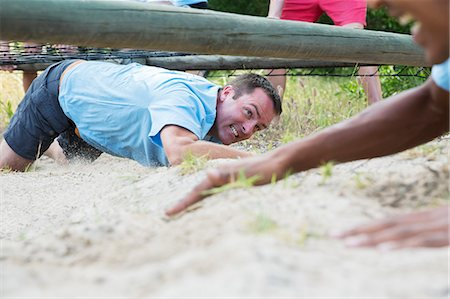 Determined man crawling under net on boot camp obstacle course Stock Photo - Premium Royalty-Free, Code: 6113-08088098