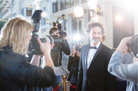 Smiling celebrity in tuxedo being photographed by paparazzi at red carpet event Stock Photo - Premium Royalty-Free, Code: 6113-08088147