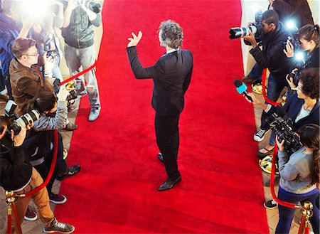 Celebrity arriving at red carpet event and waving at photographing paparazzi Stock Photo - Premium Royalty-Free, Code: 6113-08088158