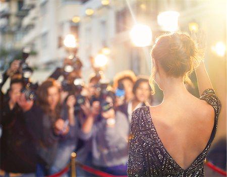Celebrity waving at paparazzi photographers at event Stock Photo - Premium Royalty-Free, Code: 6113-08088172