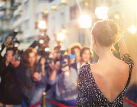 Celebrity waving at paparazzi photographers at event Stock Photo - Premium Royalty-Free, Code: 6113-08088172