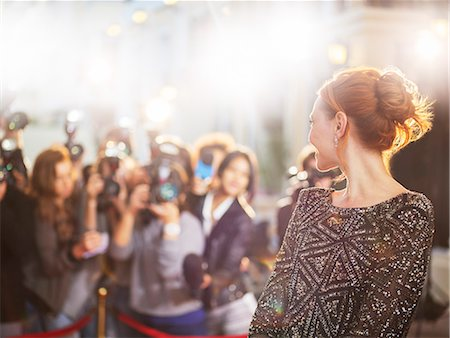 Celebrity turning and smiling at paparazzi photographers at event Stock Photo - Premium Royalty-Free, Code: 6113-08088182