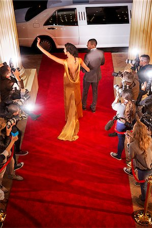 Celebrity couple waving to paparazzi photographers and leaving red carpet event Stock Photo - Premium Royalty-Free, Code: 6113-08088189