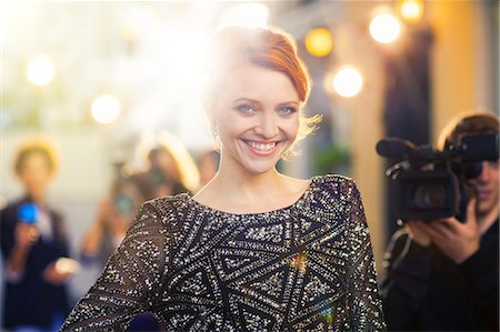 Portrait of smiling celebrity being photographed by paparazzi at event Stock Photo - Premium Royalty-Free, Code: 6113-08088190