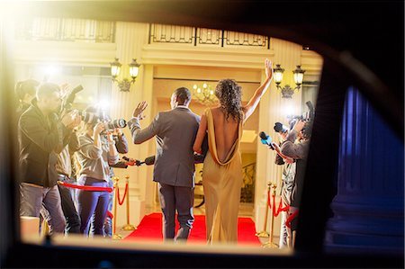 Celebrity couple arriving and waving to paparazzi photographers at red carpet event Stock Photo - Premium Royalty-Free, Code: 6113-08088191
