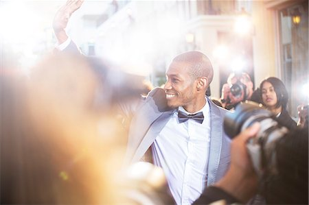 Smiling celebrity waving to paparazzi photographers at event Stock Photo - Premium Royalty-Free, Code: 6113-08088197