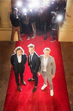 Portrait of smiling celebrities posing on red carpet Stock Photo - Premium Royalty-Free, Code: 6113-08088256