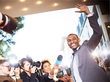 Waving celebrity being interviewed and photographed by paparazzi at event Stock Photo - Premium Royalty-Free, Code: 6113-08088203