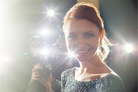 Close up portrait of smiling celebrity being photographed at paparazzi event Stock Photo - Premium Royalty-Free, Code: 6113-08088200