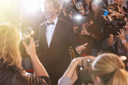 Smiling celebrity posing for paparazzi photographers at event Stock Photo - Premium Royalty-Free, Code: 6113-08088208