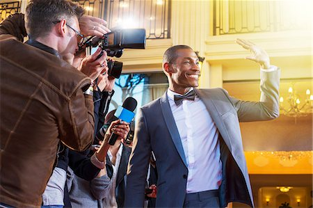Celebrity waving and being photographed by paparazzi photographers Stock Photo - Premium Royalty-Free, Code: 6113-08088216