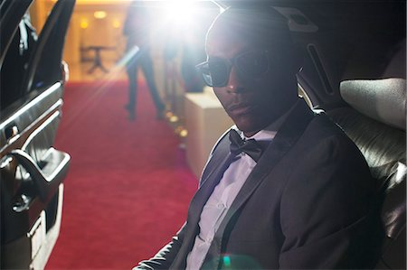 Portrait of serious celebrity in sunglasses inside limousine arriving at red carpet event Stock Photo - Premium Royalty-Free, Code: 6113-08088225