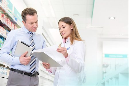 Pharmacist and manager reviewing paperwork in pharmacy Stock Photo - Premium Royalty-Free, Code: 6113-08088370