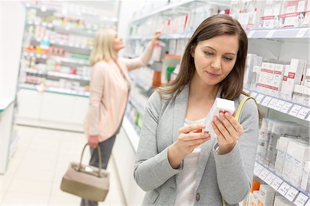 Customer reading label on box in pharmacy Stock Photo - Premium Royalty-Free, Code: 6113-08088375
