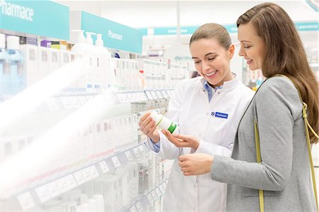 Pharmacist and customer reviewing label on bottle in pharmacy Stock Photo - Premium Royalty-Free, Code: 6113-08088388