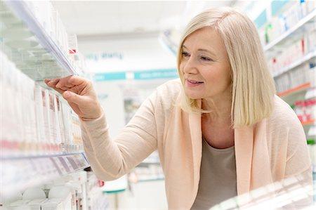 Customer reaching for box on shelf in pharmacy Stock Photo - Premium Royalty-Free, Code: 6113-08088392