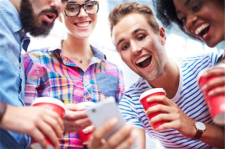 Friends laughing and drinking coffee around cell phone Stock Photo - Premium Royalty-Free, Code: 6113-08088492