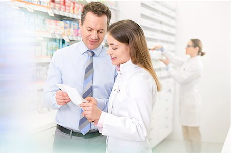 Pharmacist and customer reviewing prescription in pharmacy Stock Photo - Premium Royalty-Free, Code: 6113-08088404